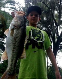 Happy young angler with large bass caught on guided bass trip in winter haven just south of Orlando Florida